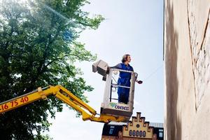 """2011. Maria Kanervo skriver """"Tell me"""" på en fasad."""