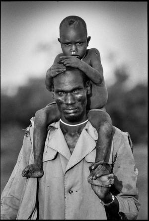 Sydöstra Sudan. En man ur stammen Dinka flyr med sin son genom träsket nära Nasir medans inbördeskriget rasar.Bilden är tagen 1996.