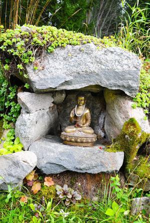 En buddhastaty brukar kanske inte vanligtvis vara omgiven av mossa och lingonris – det är den i Gässlingsbo.