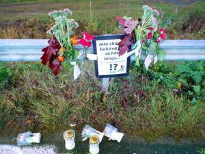 Fejkad olycksplats med blommor och ljus.