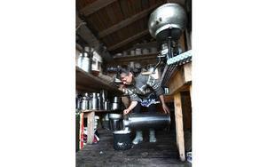Yvonne fyller på mjölk som ska pastöriseras för att hon ska kunna göra filmjölk av den. Foto: Bons Nisse Andersson