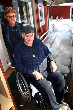 Birger Nilsson i Rastorp är instängd i huset på grund av snöras som blockerar rullstolsrampen. Kommunen satte aldrig upp något snörasskydd på taket. Sambon Barbro Andersson hjälper till så mycket hon kan.