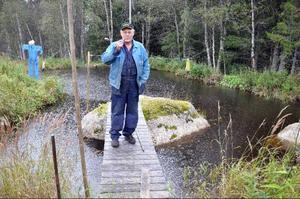 """Ola Jonsson vid sin lilla fiskodlingssjö. """"Här kan jag sitta timtals och prata med fisken""""."""