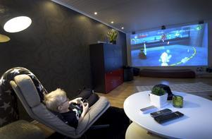 Gillestugan fungerar som både gästrum och tv-rum. En vägg har svart och grå-möstrad tapet som lyses upp av spotlights från taket, övriga väggar är ljusa.