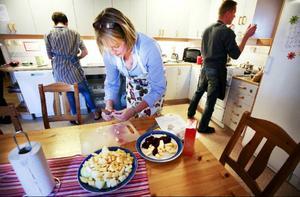 Eva Peterson skär kål och rödbetor som sedan ska bli ugnsrostade. I bakgrunden syns Rikard Bogataj och Janne Olsson.