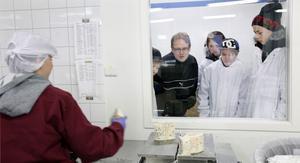 """Företagsbesök. Ockelbo Osts delägare Fredrik Ström berättar för eleverna Fredrik Agstam, Martina Hellberg och Tom Haglund om hur det går till när osten packas"""". Den där osten vill vi inte ha eftersom den har mögel på sig även på ovansidan. Men det är inget fel på den, men den ser inte snygg ut"""", förklarar Fredrik Ström"""