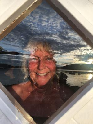 Moln, himmel och sjö reflekterar i bastufönstret där Eva Fermh från Västerås tittar ut. Bilden är tagen i Stavre, Jämtland.