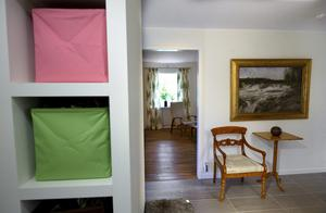 Stengolv möter trä. Från hallen ser man in i vardagsrummet. De antika möblerna och tavlorna i huset är arvegods från Kristinas morfar.