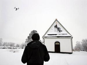 Minihelikoptern har börjat stiga över Frösö kyrka för att ta sina bilder. Tobias styr maskinen med säker hand.