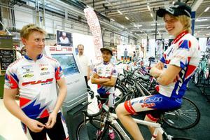 """Viktor Danebäck, Ice Karlsson och Jon """"Jämtland"""" Gunnarsson demonstrerar det senaste inom cykelsporten. En simulator där klassiska cykeletapper finns inlagrade – både med motstånd till trampor och med rätta bilder till skärm. Det enda som saknas är Europsports Roberto Vacchi och Anders Adamsson som kommenterar vilka kläder man har när man sitter på sadeln. Vilket kanske är tur."""