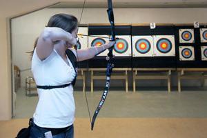 Guldmedaljören Lina Björklund visar hur det ska se ut när man tränar bågskytte.