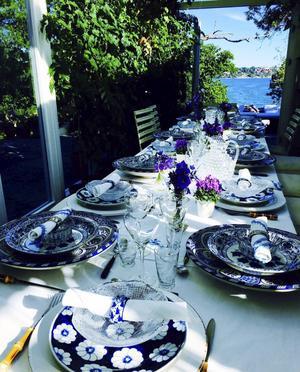 Fynd från flera utlandsresor hittas på bordet. De stora, rundade tallrikarna handmålade i blått och vitt är köpta i Marrakech. Huvudrättstallriken ovanpå kommer från Hanoi och servettringarna från Tel Aviv. De handbroderade servetterna och bordsduken är införskaffade i Palma.