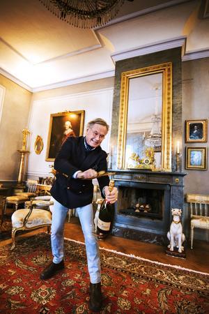 FRONTBILD! Ömsom allvarlig och ömsom skämtsam. Här svingar Robert Montgomery-Cederhielm Karl XI:s barndomssvärd över en champagneflaska.