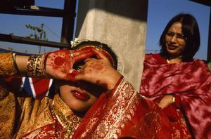 En newarflicka från Katmandu, Nepal, som rituellt visar sitt ansikte för solguden Surya. Det är en del av den ritual som alla newarflickor går igenom i samband med sin första menstruation.