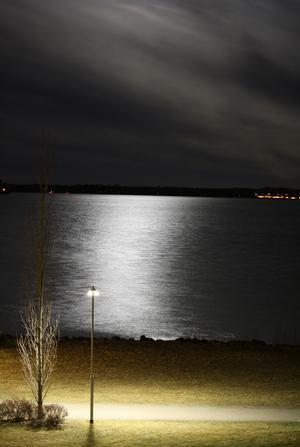 Ljussättningen blir speciellt nattetid ofta mycket vacker som i denna bild med fullmåne bakom molnskyar och med en mångata i mjuk kontrast till gatlampans sken