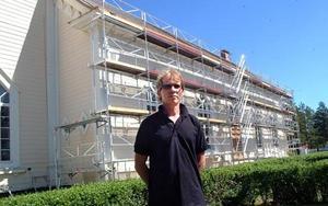 Bräcke församlings Ronny Abrahamsson framför Bräcke kyrka som nu utrustats med byggställningar inför den väntande tak- och fasadmålningen.