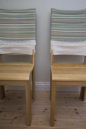 I köket står de egendesignade stolarna med vävda ryggstöd.