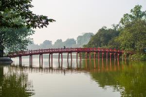 Den röda gångbron leder till en liten tempelö i sjön Hoan Kiem mitt i stan.