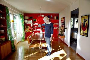 Lisa Rönnkvist i vardagsrummet. Hyllsystemet i har Johan byggt av sprayfärgade Elfa-skenor och hyllplan som han fanerat själv.