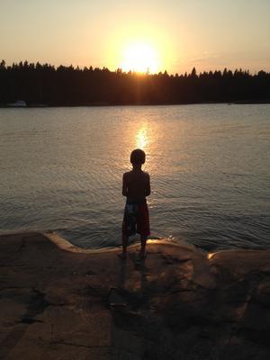 Daniel står och fiskar i solnedgången.