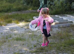 Philippa har hittat plast som hon skyndar iväg till sopsäcken med.