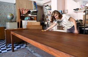 Anna Löfstrand, möbelsnickare och möbelrenoverare, restaurerar ett bord åt en kund. Hon har skrapat bort ett tjockt lager med olja och bets, sedan lagt på teakbets och hårdvaxolja utan pigment.