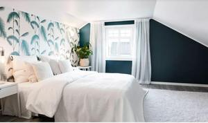 Sovrummet är inrett med en stormönstrad tapet och ljusa textiler. Foto: Hoome mäkleri