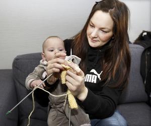 Emma, fyra månader är i särklass yngst på kursen och hon tittar intresserat på när mamma Susanne Nilsson från Frösön skapar en mössa.Foto: Jan Andersson