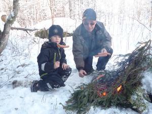 Morfar Claes har pulsat i snön med Simon över gärden och in i skogen  och grillar korv vid Ugglestenen. Det var -16C.