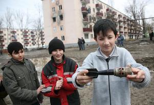 Arkivbild. Tre barn visar upp en granat de hittat i Tjetjenien i Ryssland  2007. Barnen på bilden har inget med artikeln att göra.