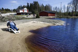 Sandstranden vid den lilla plaskdammen är färdigställd. Här är vattnet bara drygt en meter djupt. I bakgrunden syns Johnnys nybyggda villa där han också har sitt kontor.