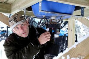 Viltvårdaren Mikael Folkesson kontrollerar den tidsstyrda utrustningen som släpper ut spannmål till djuren. BILD: SAMUEL BORG