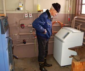 Jordvärmepumpen är liten till formatet då den inte har någon ackumulatortank. Olle Andersson läser intresserat av vad pumpen ger för tillfället.
