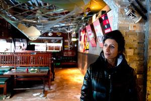 Angel Demir betraktar förödelsen i restaurangen som hon äger tillsammans med sin man Dogan Demir.