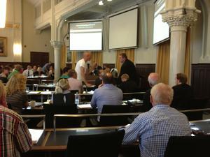 Staffan Werme (FP) står i ett samtal med en sittande Anders Åhrlin (M) och Jonas Millard (SD).