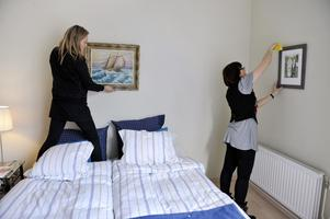 Två stylister från en inredningsfirma jobbar med homestyling inför en bostadsvisning.