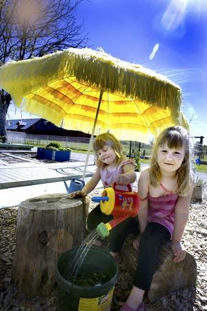 UNDER PARASOLLET. Sara Lundqvist, fyra år och Tyra Lindgren, fem år leker gärna under parasollet där några stubbar fungerar fint som bord och stolar. Här kan barnen också leka med vatten.