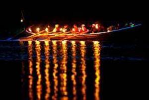 Foto:NICK BLACKMON Upplyst. Elfkarleby kyrkbåtsroddare hakade på den nordligare traditionen med lyskväll längs kusten. Med 16 facklor längs sidorna rodde man uppströms från Skutskär till Älvkarleby.
