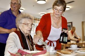 Nu är det serverat. Vera Jensen häller upp dricka åt Marianne Erlandsson.
