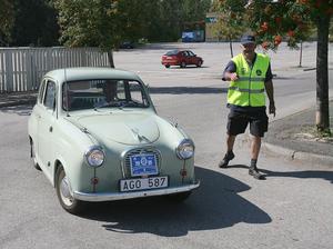 Sven Jonsson med sin Austin A35 från 1957 vinkas in i mål av funktionären Åke Älgh.