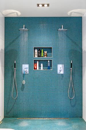 Paret duschar gärna tillsammans så de gjorde en stor dubbeldusch. Med mosaik i favoritfärgen petroleum.