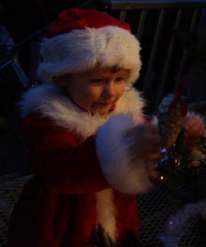 Detta är ett foto på en liten prinsessa på 3 år som firande Lucia på sitt dagis. Mitt i allt stök fick hon syn på en julgran och bestämde sig för att detta kräver en närmare titt. Hon blev helt tagen av hur fina juldekorationerna var.