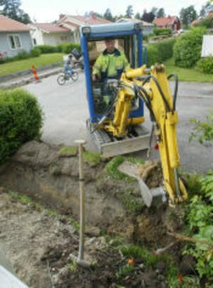 Christian Karlsson tar plats i grävaren som ska göra ett dike för rören den sista biten in till ett av husen på Glimmervägen i Sidsjön.