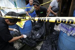 En begravningsbyrå bär bort en liksäck efter ett drogtillslag som resulterade i att två bröder och en oidentifierad person dödades av polisen i oktober förra året.