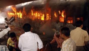Tåg sattes i brand av upprörda resenärer.Foto: Aftab Alam Siddiqui/AP/Scanpix
