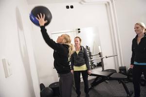 Medicinbollen ska högt upp mot väggen. Malin Sjökvist visar och Amelie Saether och Evelina Sjödin gör sig redo att köra hårt på övningen.