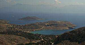 Vy över strandbukten Pondamos och byn Emborio på Chalki, med Rhodos i bakgrunden.