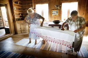Ingvor Westerström och Inger Eriksson sätter upp textilier inför sommaren i Per-Nilsasgården.