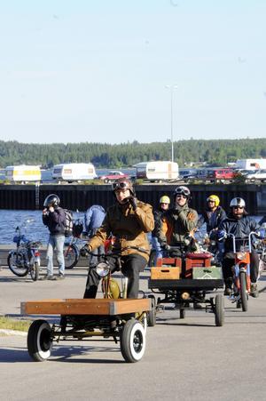 En karavan av veteranmopeder lämnar Hudiksvallskajen, med Mattias Lönnman och hans unika flakmoped i täten.