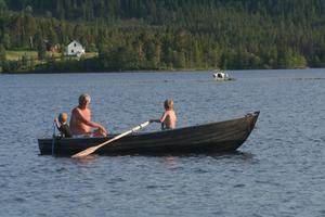 Magnus Liljemark 7 år ror träekan och i båten sitter Lillebror Fredrik och Kompisen Lorentz. I bakgrunden svalkar sig två fjällkorskalvar.
